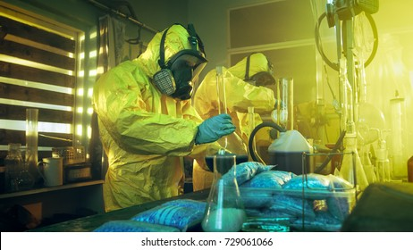 In the Underground Laboratory Two Clandestine Chemists Wearing Protective Coveralls and Masks Cook Drugs. They Work with Beakers, Distillation Glassware, Canisters and Hosepipe. True Crime Concept.