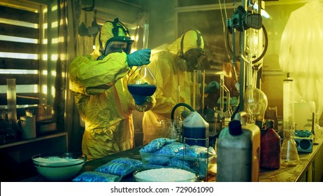 In the Underground Laboratory Two Clandestine Chemists Cook Drugs. They Wear Masks and Coveralls and Work with Beakers and Toxic Chemical Compounds.