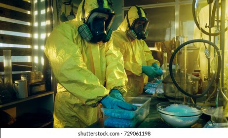 In the Underground Laboratory Two Clandestine Chemists Wearing Protective Masks and Coveralls Pack Bags of Synthesised Crystal Meth into Boxes for Further Distribution. Laboratory Full of Equipment.
