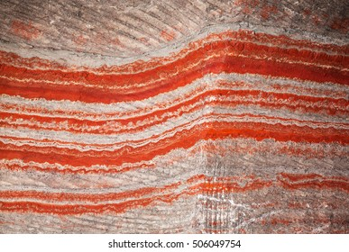 Underground multicolor fragment of wall in potassium salt mine with stripes, background