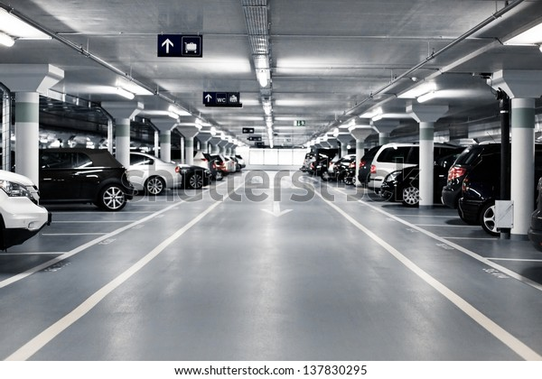 Underground parking with cars. White colors.