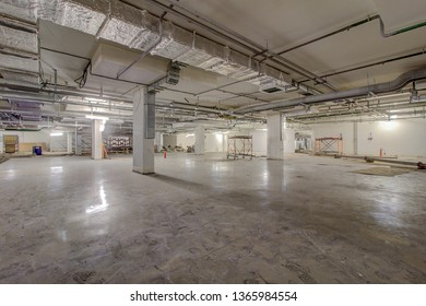 Underground parking under construction. Empty Industrial Shed or Parking Lot. Urban, Rough construction. Empty Warehouse Interior. Vintage Style. screeding is process person called concrete finisher.