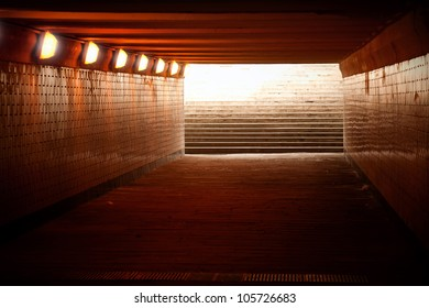 Underground passage with lights and stairs in glowing end