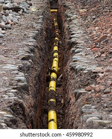 Underground services yellow Gas Polyethylene Pipe being sunk into the ground under the frost line.