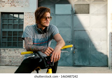 Underground subculture, cool punker tattooed man on bike, with headphones