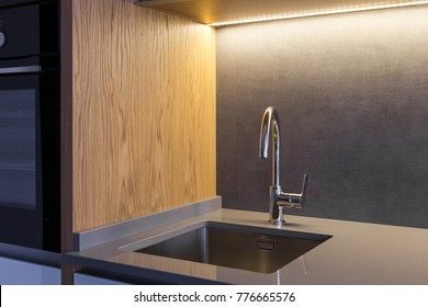 An undermounted sink and a mixer mounted in a stone ceramic countertop in a modern loft kitchen in grey color with wooden details.