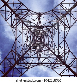 Underneath an electricity pylon showing the symmetrical pattern of the tower above. Blue sky and clouds.