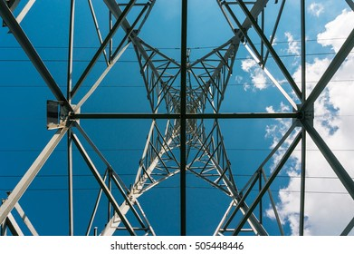 Underneath transmission tower for overhead high voltage electrical power lines with blue skies and clouds.