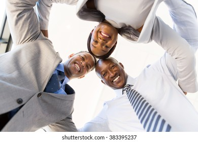 underneath view of businesspeople in a circle looking down