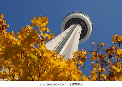 The underside of the observation deck of the CN Tower, the world's tallest freestanding structure, framed by maple leaves and set against a blue sky in Toronto, Ontario, Canada.