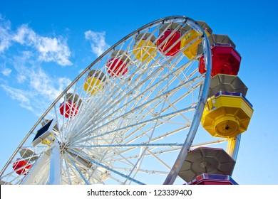 Underside view of a ferris wheel rotating downward on California's Santa Monica Pier.