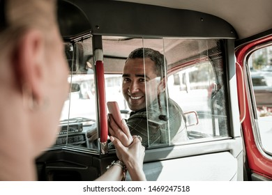 Understanding each other. Car driver looking back at the woman on a backseat and smiling to her showing him her smartphone.