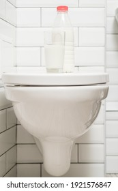 Understanding lactose intolerance. A glass of milk and a bottle of dairy product are on the toilet lid.
