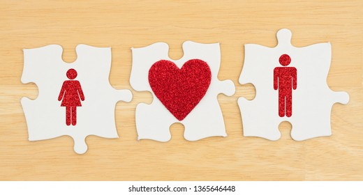 Understanding romance, Three puzzle pieces with a heart and a man and woman on textured desk wood background