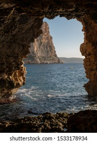 Underwater cave with stone arches carved into the cliff by the sea. cala moraig