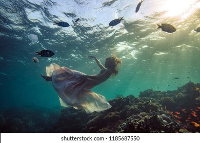 Underwater fashion girl in long dress sinking