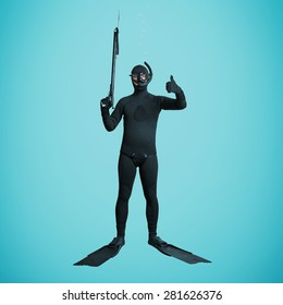 underwater fisherman in full equipment with spear fishing gun showing thumbs up over blue background