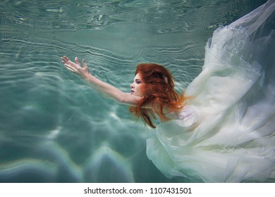 Underwater girl. Beautiful red-haired woman in a white dress, swimming under water. Nymph or mermaid, fantasy concept.