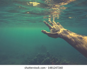 Underwater hand reaching for sun. Man drowning in the sea. Rescue from swimming pool accident. Sinking under the water. Shipwreck survivor. Need help. Believe in your self. Quote background template.