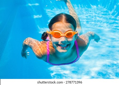Underwater happy cute girl in swimming pool