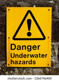 Underwater hazards warning sign at a river estuary