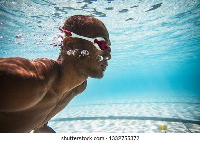 Underwater image of a male swimmer diving and swimming in a swimming pool to train