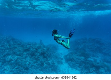 Underwater image of a young lady snorkeling and diving in a tropical sea with hands on legs. Beautiful woman body under water.