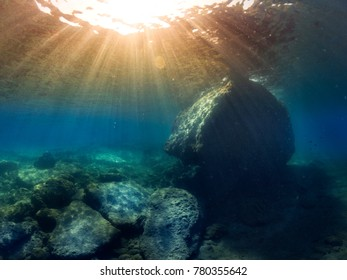 Underwater landscape and a big rock with sunlight rays.