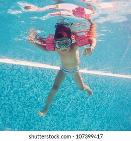 Underwater little kid in swimming pool with musk and armrests.