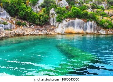 Underwater Lycia ruins of ancient Simena - turkish island Kekova (Caravola), near Demre, Antalya province, Turkey. Old destroyed walls of houses, rocks, bright clear blue water and beautiful plants