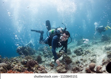 Underwater ocean scene with gas bubbles and divers.