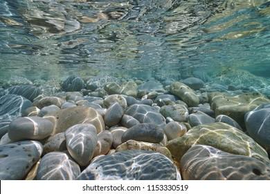 Underwater pebbles and rocks below water surface on the seashore, Mediterranean sea, Costa Blanca, Javea, Alicante