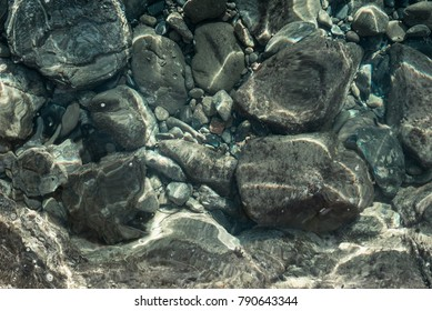 Underwater pebbles texture. Background. Water reflections.