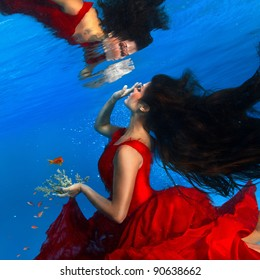 underwater photo beautiful brunette wearing red dress looking on her mirror at water surface