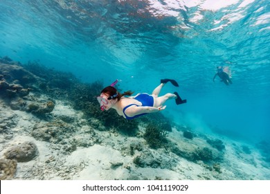 Underwater photo of family mother and daughter snorkeling in a clear tropical water at coral reef