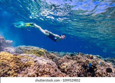 Underwater photo of family mother and son snorkeling in a clear tropical water at coral reef