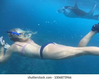 Photo sous-marine d'une fille faisant du snorkeling avec une raie de mante au-dessus du récif à Nusa Penida, Bali, Indonésie