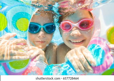 underwater photo of  little kids  swimming  in pool