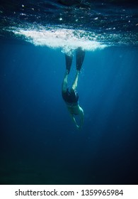 underwater photo of male dives into deep blue sea