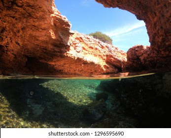 Underwater photo of tropical cave with emerald clear sea and coral reef