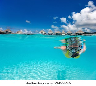 Underwater photo of woman snorkeling in clear tropical waters in front of overwater villas