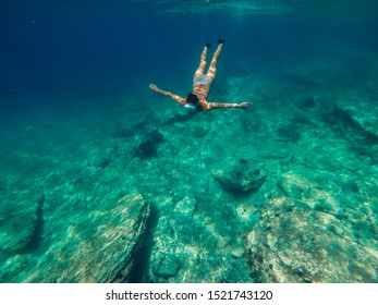 Underwater photo of a woman wearing stripe swimsuit diving into the shallow sea water