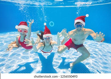 underwater photo of young family with kid in Santa hat in swimming  pool