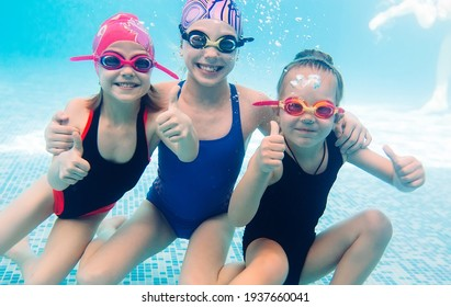 Underwater photo of young friends in swimming pool