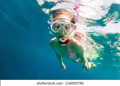 Underwater photo of young girl swimming and snorkeling in tropical ocean