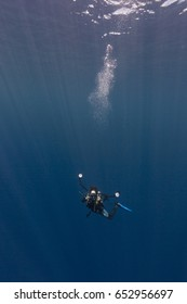 Underwater Photographer in blue water with sun beams