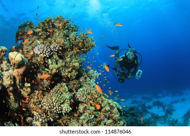 Underwater Photographer scuba diving with camera on coral reef in ocean