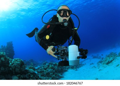 Underwater Photographer scuba diving with camera