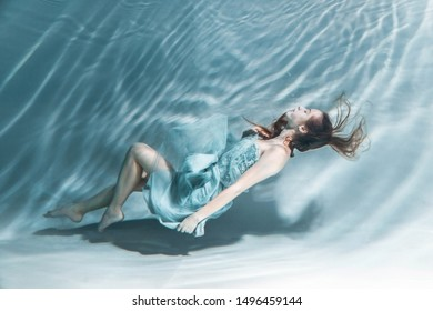 underwater photography.  girl in dress posing underwater