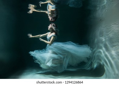 underwater photography. Girl mermaid. model in wate .In a blue flying dress. on dark background